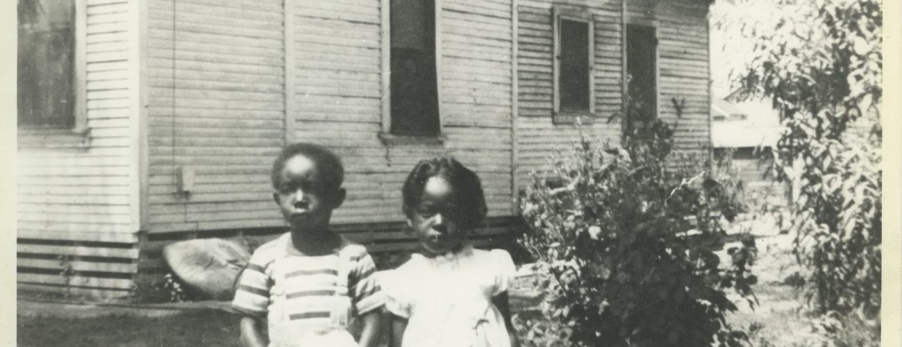 Two children in front of house